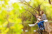 Boy and girl together near the pond play with paper boats on the water in beautiful forest landscape
