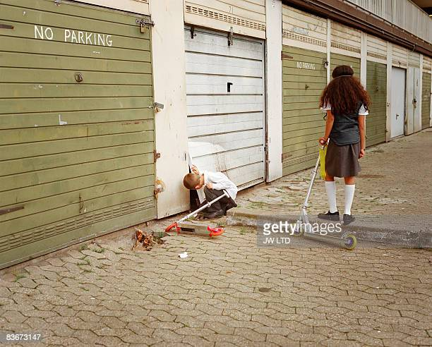 Boy and girl playing by garage doors on housing estate