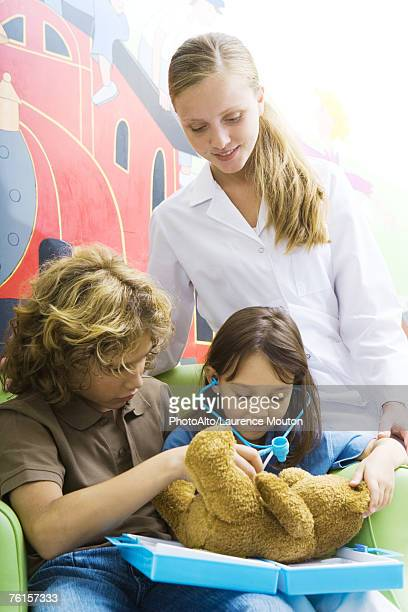 Boy and girl playing doctor with teddy bear