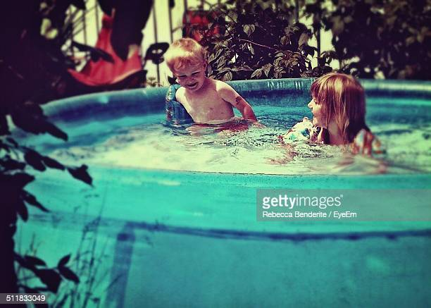 Boy and girl playing in a large bathtub