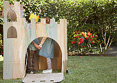 Boy and girl (6-7) playing in cardboard castle in garden