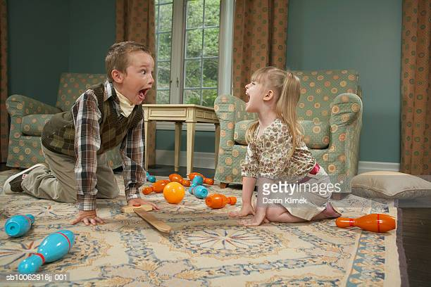 Boy and girl (4-6) playing in living room, kneeling on carpet and yelling