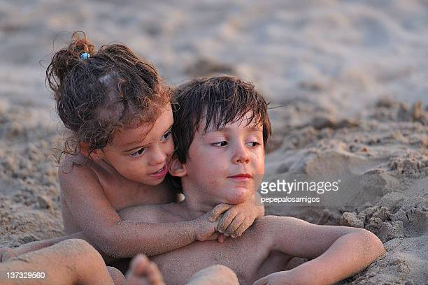 Boy and girl playing in sand, Spain