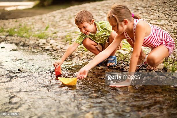 Garçon et fille jouant papier Bateaux sur la rivière
