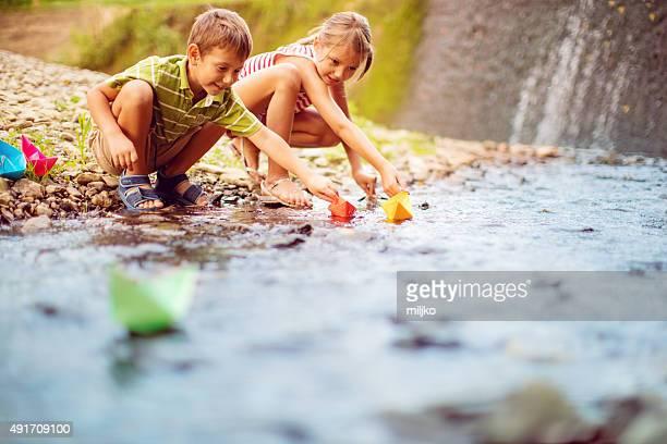 Ragazzo e ragazza giocare carta imbarcazioni lungo il fiume
