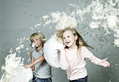 Boy and girl (6-9) playing pillow fight