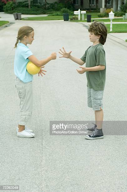 Boy and girl playing rock paper scissors in residential street