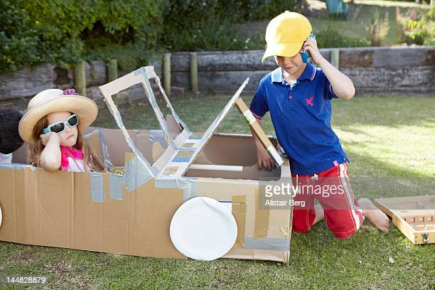 Boy and girl playing with a cardboard car