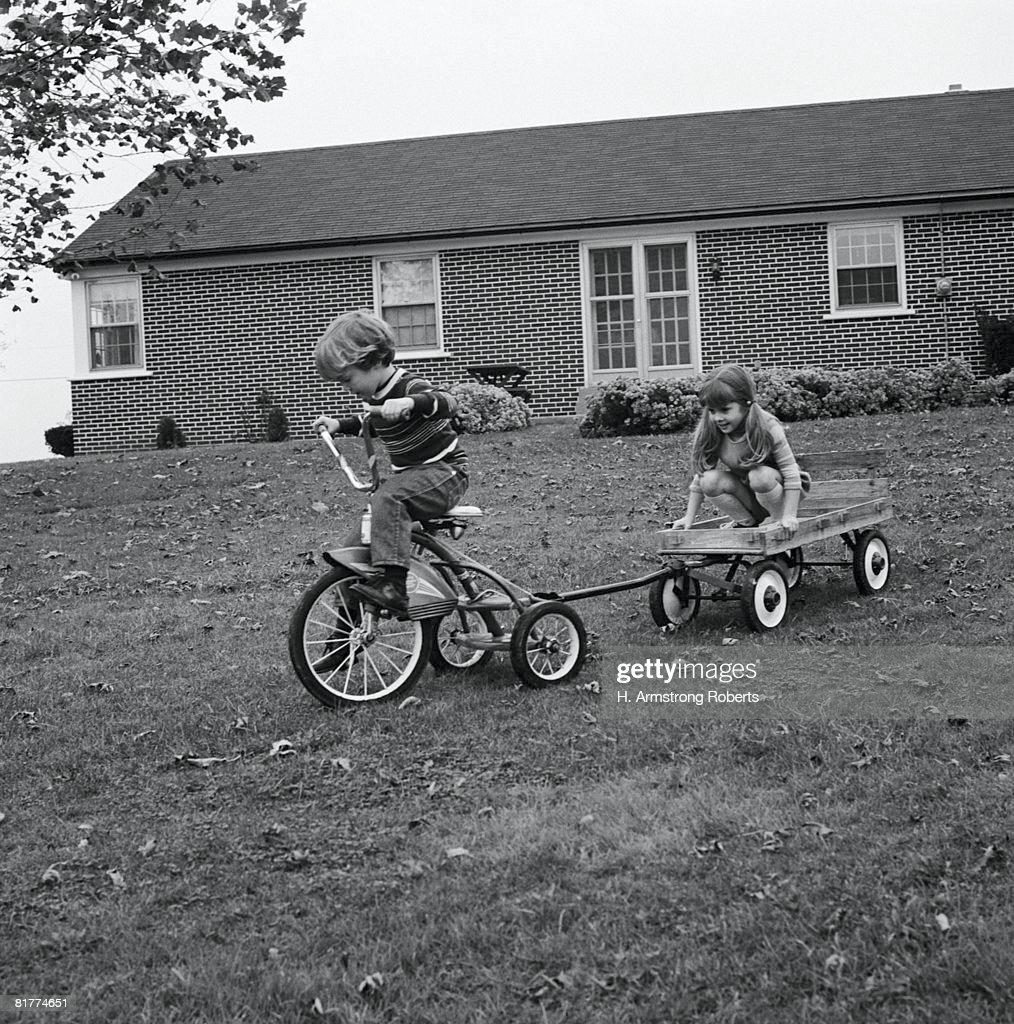 Boy and girl playing with cycle and pull wagon. : Stock Photo