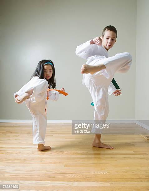 Boy and girl (4-9) practising Taekwondo kicks