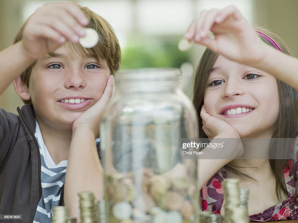 Boy and girl putting coins in jar : Stock Photo