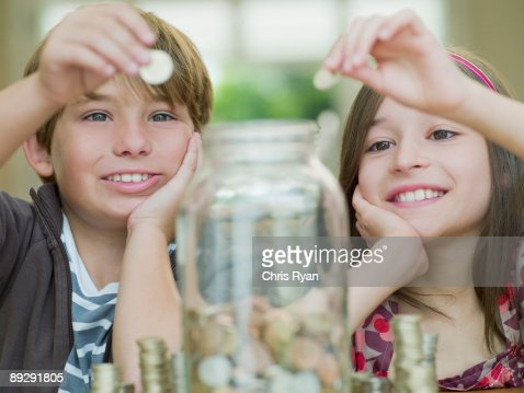 Boy and girl putting coins in jar : Photo