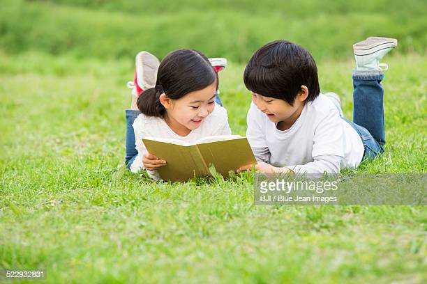 Boy and girl reading on the grass