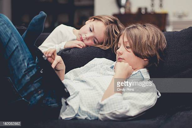 Boy and girl relaxing on the couch with a tablet