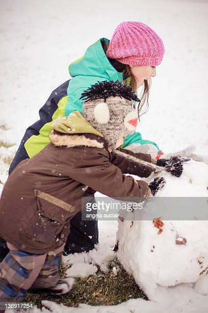 Boy and girl roll bottom ball of snowman