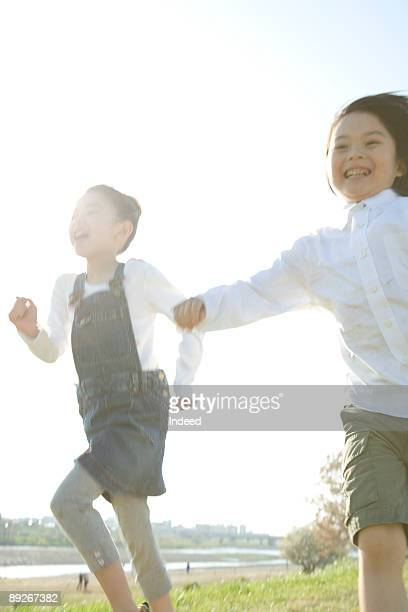 Boy and girl (6-9) running at side of river