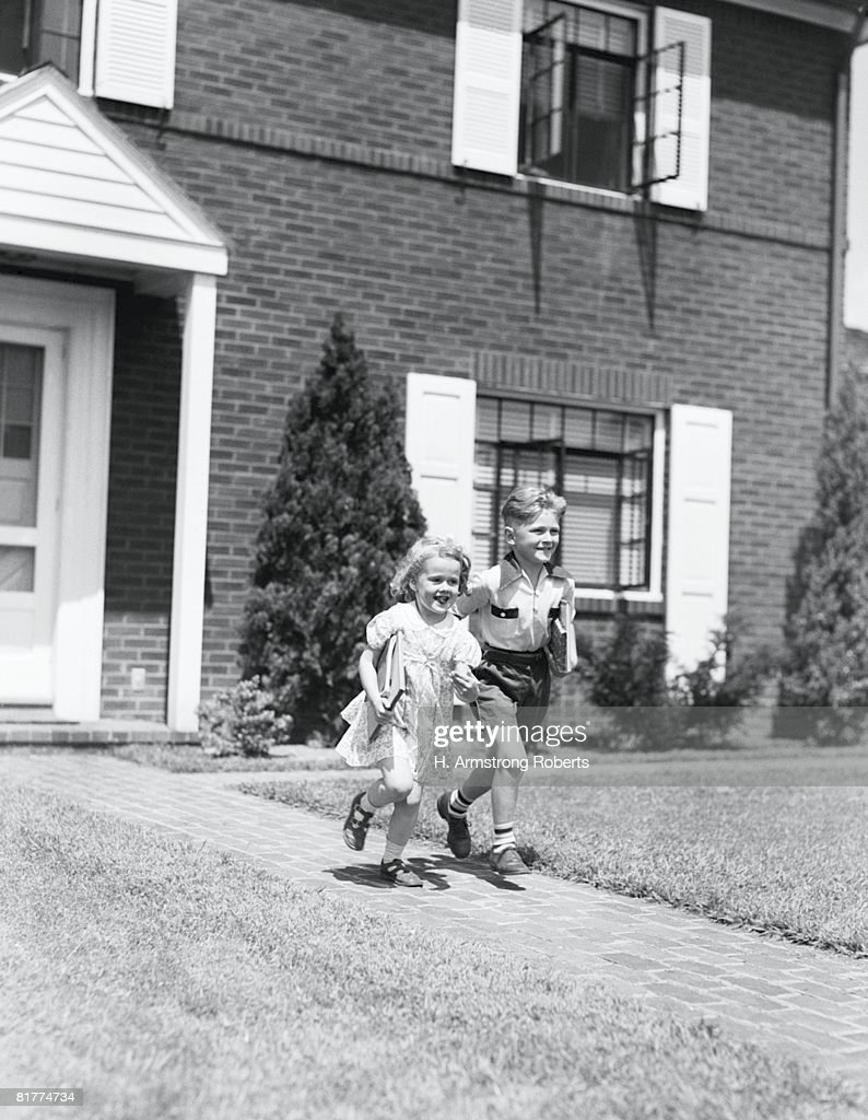 Boy and girl running down sidewalk, holding school books, going to school. : Stock Photo