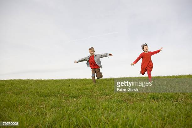 'Boy (10-12) and girl (7-9) running in meadow, arms outstretched'