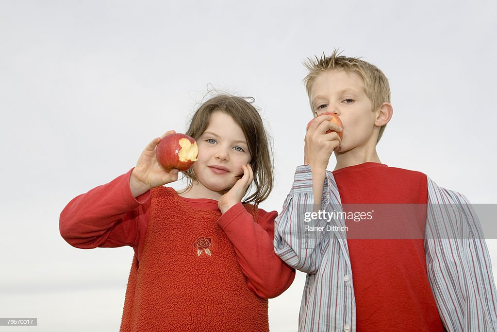 Boy (10-12) and girl (7-9) eating apple : Stock Photo