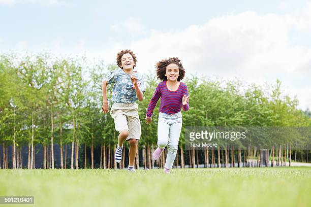 boy and girl running in park
