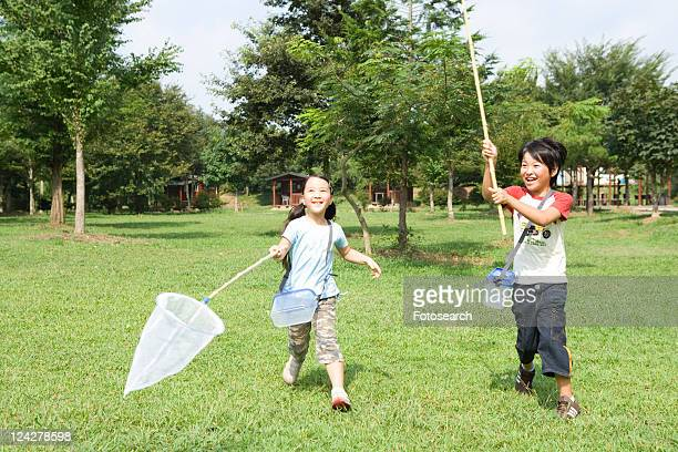 Boy and girl running with butterfly net