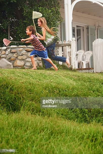 Boy and Girl Running with Butterfly Nets