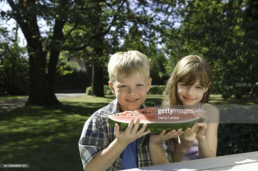 Boy and girl (6-8) sharing watermelon in garden : Stock Photo