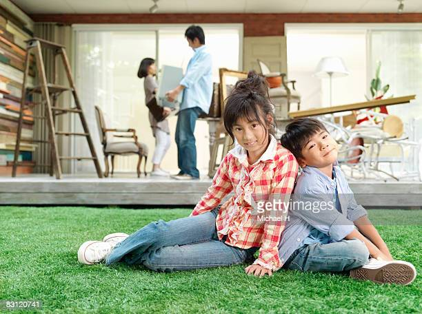 Boy and girl sits on lawn in garden