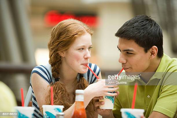 Boy and girl sitting at food court