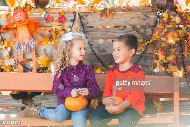 少年と秋のベンチに座っている女の子