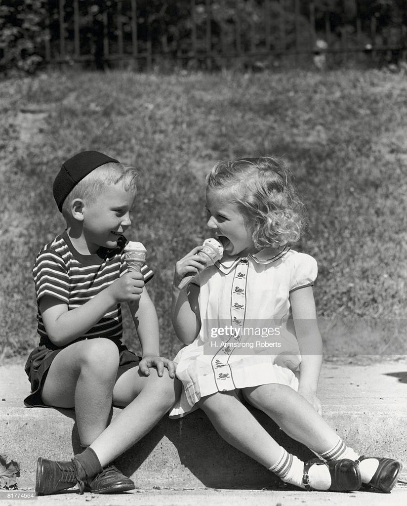 Boy and girl sitting on curb, eating ice cream cones. : Stock Photo