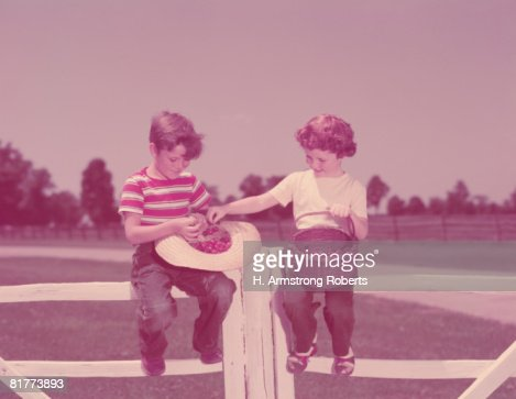 Boy and girl sitting on farm fence, with basket of cherries. (Photo by H. Armstrong Roberts/Retrofile/Getty Images) : Stock Photo