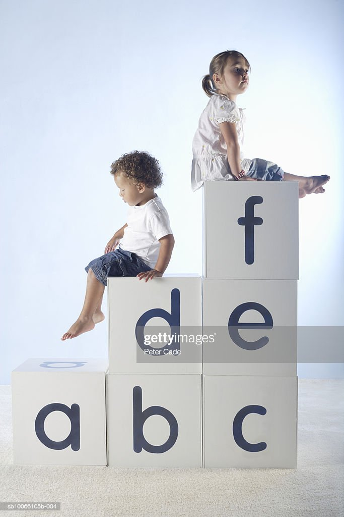Boy and girl (2-5) sitting on lettered white boxes, side view : Stock Photo
