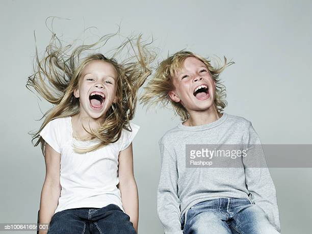 Boy and girl (6-9) sitting side by side, laughing