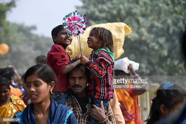 A boy and girl smile as they play with their windwheels in a country road leading away from the village of Barayarpur after they and their families...