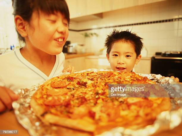 Boy and girl smiling, pizza in foreground