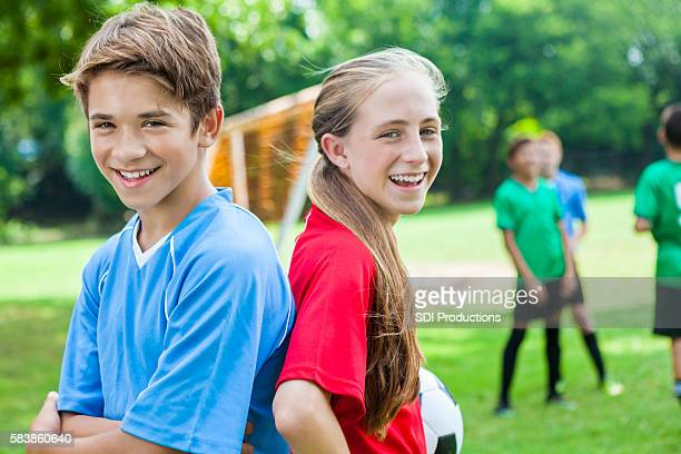 Boy and girl soccer players back to back on field