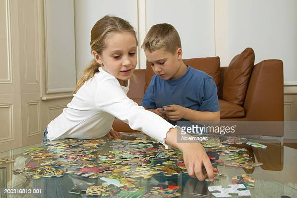 Boy and girl (6-8) solving jigsaw puzzle