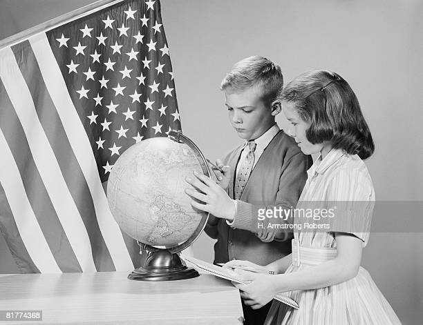 Boy and girl standing at desk, looking at globe, American flag in background. (Photo by H. Armstrong Roberts/Retrofile/Getty Images)