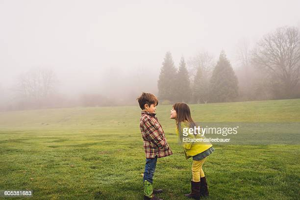 Boy and girl standing face to face in park on a foggy day