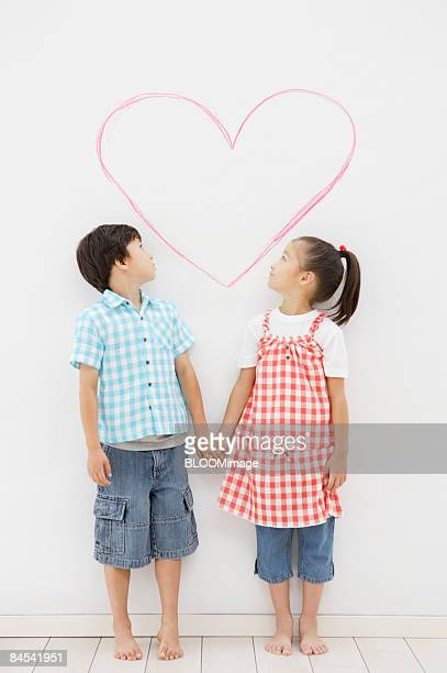 Boy and girl standing hand in hand in front of heart drawing