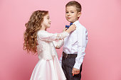 Boy and girl standing and posing in studio on pink background