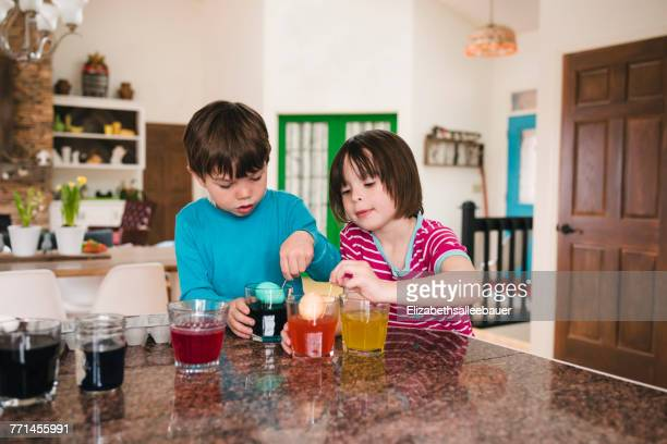 Boy and girl standing in the kitchen dying Easter eggs