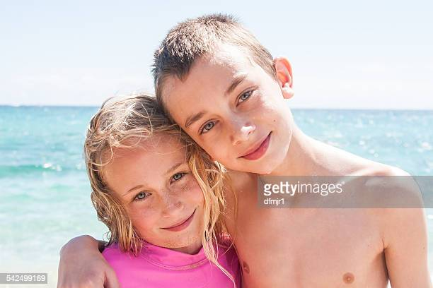 Boy and girl standing on beach hugging
