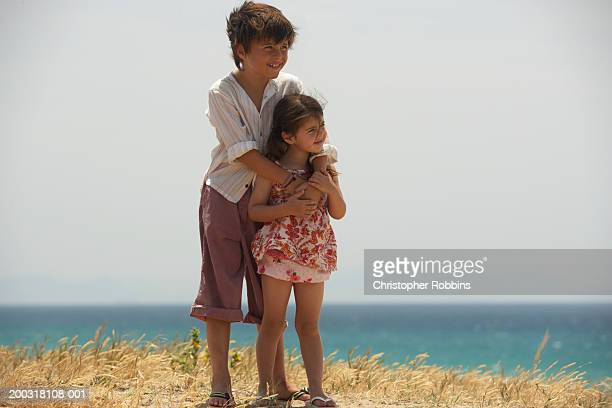 Boy (7-9) and girl (2-4) standing on dunes, smiling