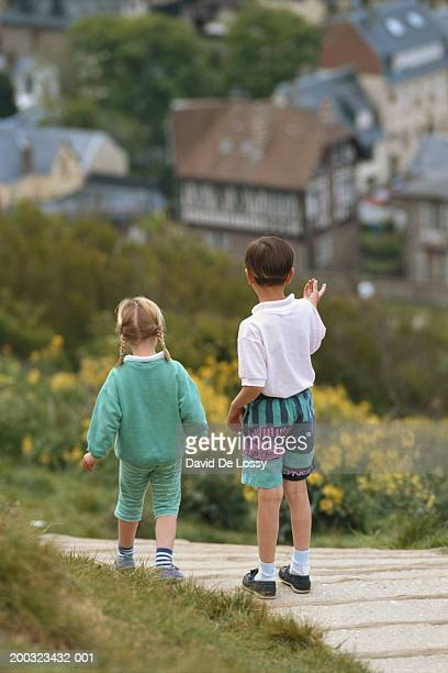 Boy and girl (3-7) standing on footpath, rear view