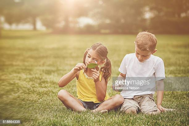 boy and girl studying nature with magnifying glass