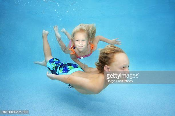 Boy and girl (4-7) swimming underwater in pool