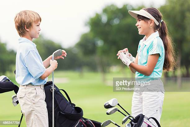 Boy and girl taking golf lessons on green course