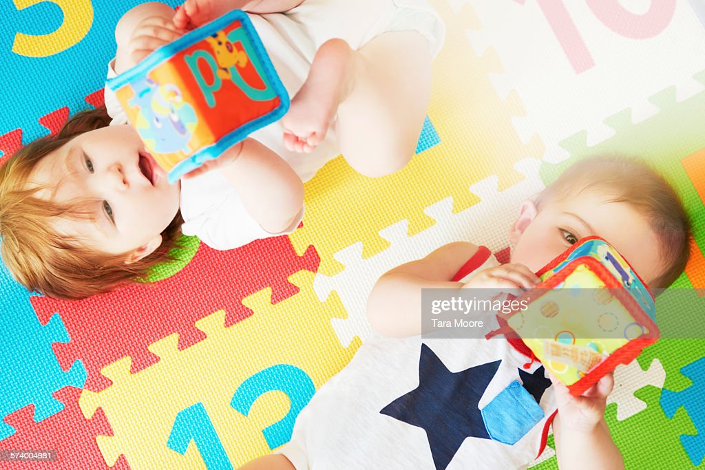 Boy and girl toddler on colorful mat playing toys : Stock Photo